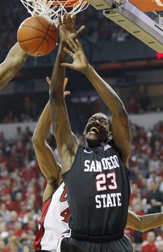 San Diego State's Deshawn Stephens gets caught under the basket by the UNLV defense during the first half of an NCAA college basketball game on Saturday, Feb. 11, 2012, in Las Vegas. (AP Photo/Isaac Brekken)
