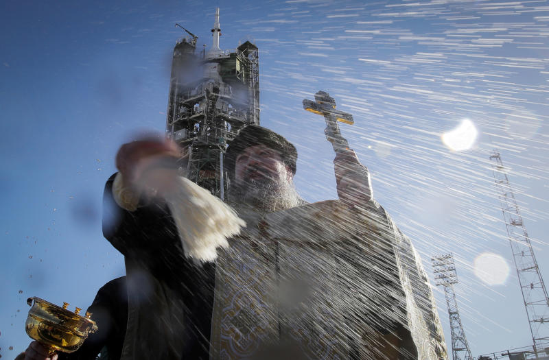 An Orthodox priest conducts a blessing service in front of the Soyuz FG rocket at the Russian leased Baikonur cosmodrome, Kazakhstan, Sunday, Dec. 2, 2018. The new Soyuz mission to the International Space Station (ISS) is scheduled on Monday, Dec. 3 with U.S. astronaut Anne McClain, Russian cosmonaut Оleg Kononenko‎ and CSA astronaut David Saint Jacques. (AP Photo/Dmitri Lovetsky)
