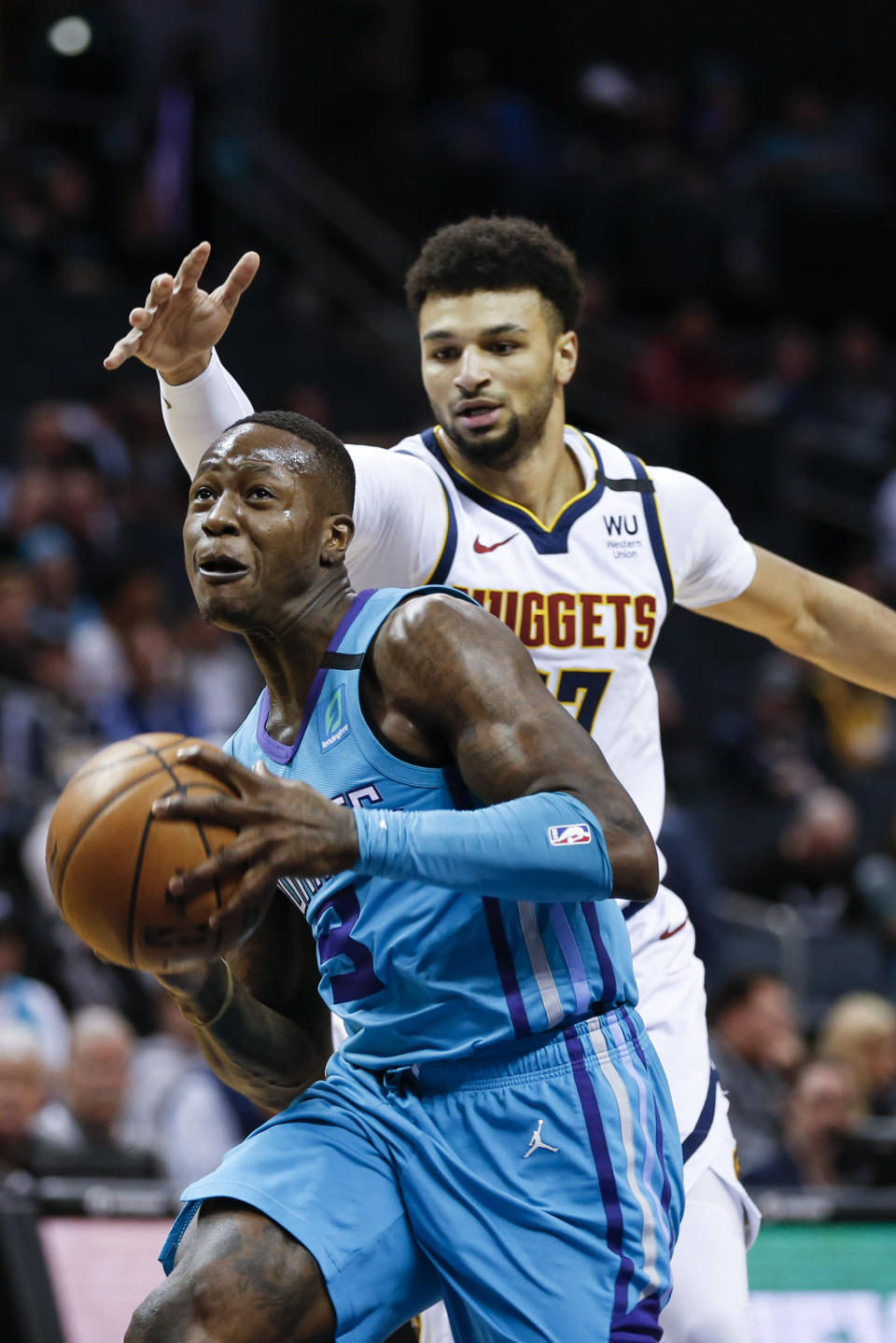 Charlotte Hornets guard Terry Rozier, left, drives to the basket ahead of Denver Nuggets guard Jamal Murray during the first half of an NBA basketball game in Charlotte, N.C., Thursday, March 5, 2020. (AP Photo/Nell Redmond)