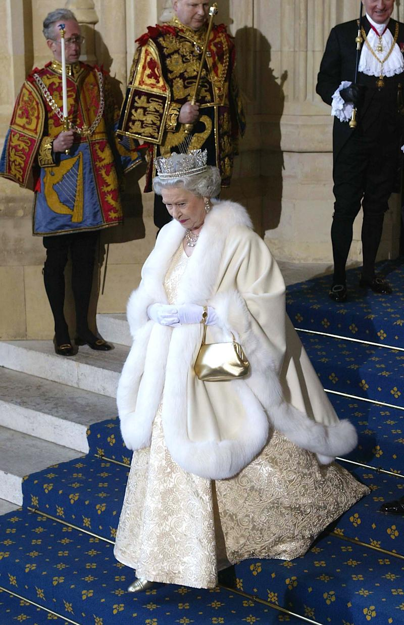 Queen Elizabeth II leaving the Houses of Parliament after its state opening, wearing a satin evening gown with a fur-trimmed robe.