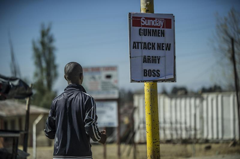 A man stands next to a newspaper headline describing the military coup in Maseru, Lesotho, on August 31, 2014 (AFP Photo/Mujahid Safodien)
