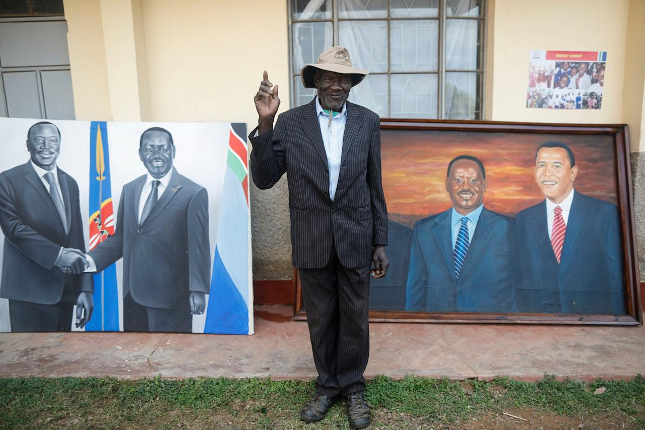 <p>A village elder poses for a photographer in front of a paiting featuring former US president Barack Obama and Kenyan opposition leader Raila Odinga (R), prior to an opening ceremony of the Sauti Kuu Sports, Vocational and Training Centre in his ancestral home Kogelo, some 400km west of the capital Nairobi, Kenya on July 16, 2018. (Photo: Dai Kurokawa/EPA-EFE/REX/Shutterstock) </p>