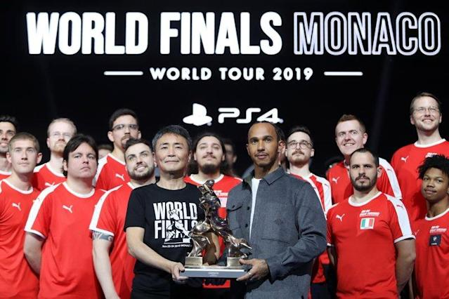 """Formula 1 Driver, Lewis Hamilton and producer of Gran Turismo, Kazunori Yamauchi pose for a photo on stage with the competitors <span class=""""copyright"""">Gran Turismo via Getty Images</span>"""