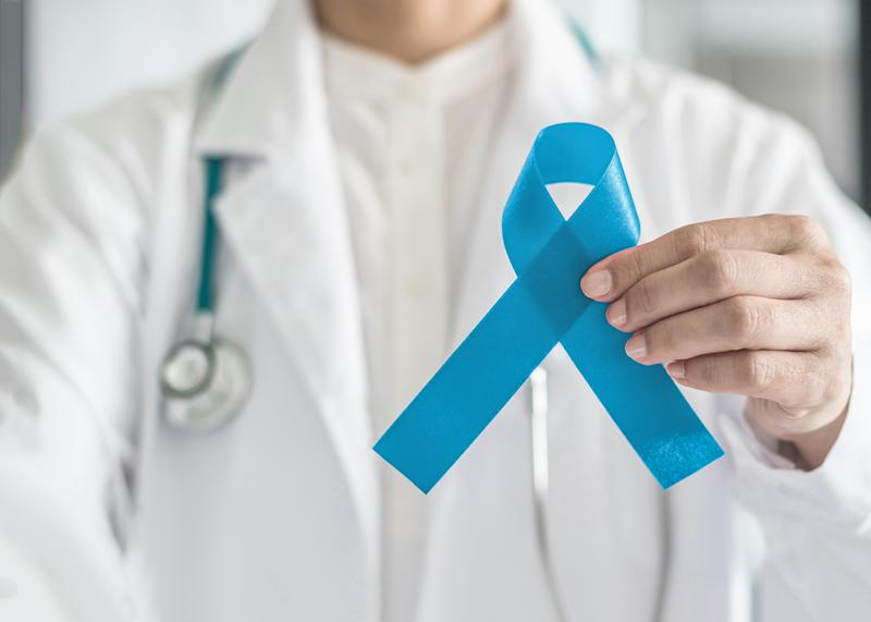 Blue ribbon symbolic for prostate cancer awareness campaign and men's health in doctor's hand