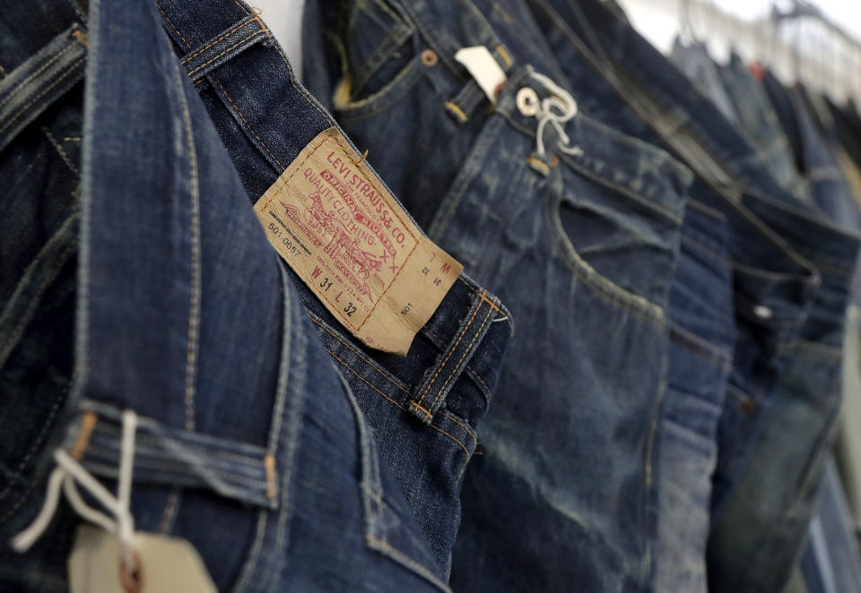 FILE- This Feb. 9, 2018 photo shows Levi's jeans hanging on a wall at Levi's innovation lab in San Francisco. On Thursday, March 21, 2019, Levi Strauss & Co. is going back to the public markets after 34 years. (AP Photo/Jeff Chiu, File)