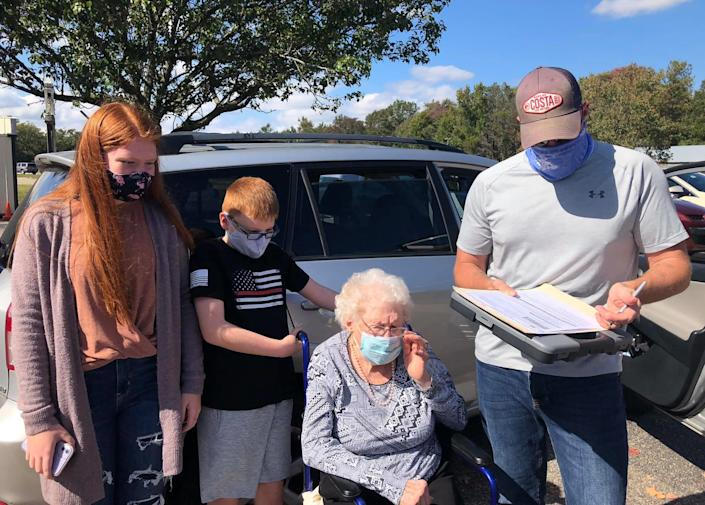 Curtis Litton fills out an 'assistance form' to be able to help his grandmother Centenarian Mabel Dorothy Duty Cook of Chesterfield complete her ballot at the Registrar's Office in Chesterfield on Oct. 15, 2020 while Cook's great-grandkids Alexa and Jack Litton witness the monumental event.