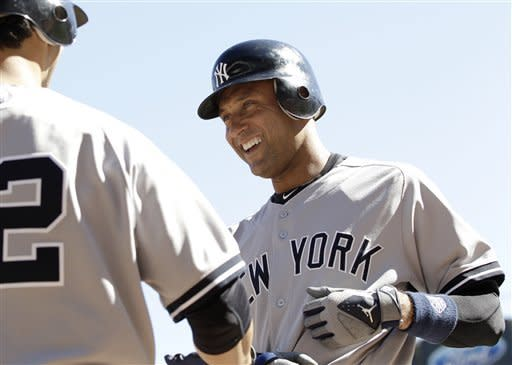 New York Yankees' Derek Jeter, right, is congratulated by Eric Chavez after he scored on a single by Nick Swisher off Minnesota Twins pitcher Brian Duensing in the third inning of a baseball game Wednesday, Sept. 26, 2012 in Minneapolis. (AP Photo/Jim Mone)