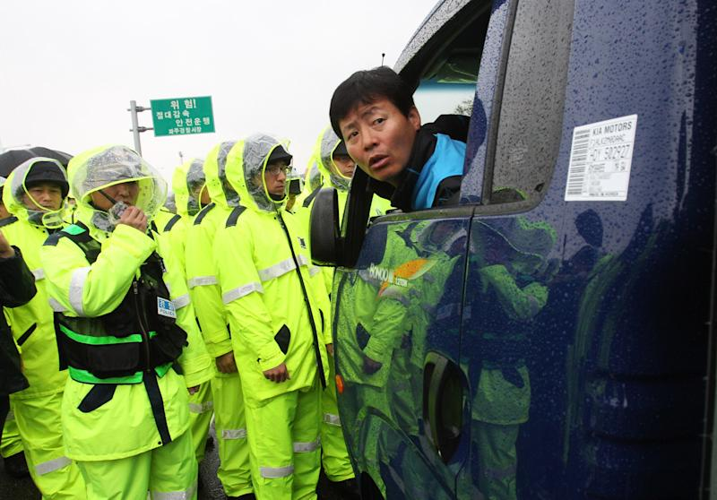 Police officers block an activist in a car carrying anti-North Korea leaflets in Paju near the demilitarized zone, South Korea, Monday, Oct. 22, 2012. South Korea banned the activists Monday from entering a border area where they planned to launch anti-Pyongyang leaflets into North Korea, an unusual move that the activists likened to surrender. (AP Photo/Ahn Young-joon)