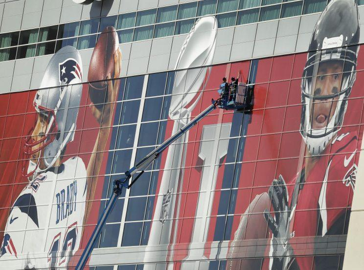 Workers attach a sign to the front of NRG Stadium as preparations continue for the NFL Super Bowl 51 football game. (AP)