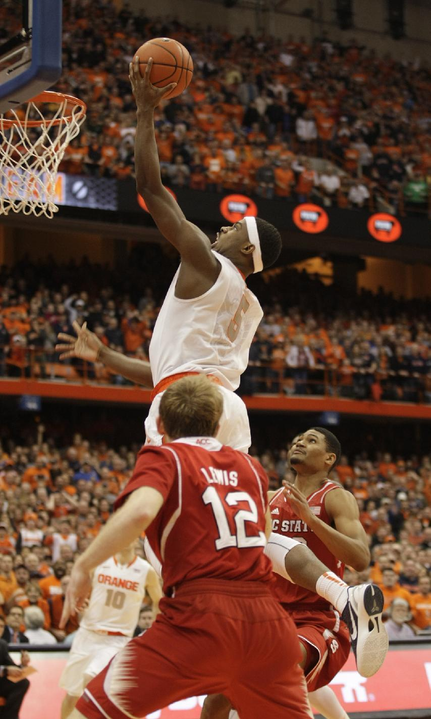 CORRECTS TO SECOND HALF, INSTEAD OF FIRST - Syracuse's C.J. Fair, top, shoots what became the winning basket against North Carolina State in the second half of an NCAA college basketball game in Syracuse, N.Y., Saturday, Feb. 15, 2014. Goaltending was called against North Carolina State's Ralston Turner on the play. Syracuse won 56-55. (AP Photo/Nick Lisi)