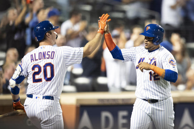New York Mets' Juan Lagares (12) celebrates with Pete Alonso (20) after scoring on a one run single by Amed Rosario during the seventh inning of a baseball game against the Cleveland Indians, Tuesday, Aug. 20, 2019, in New York. (AP Photo/Mary Altaffer)