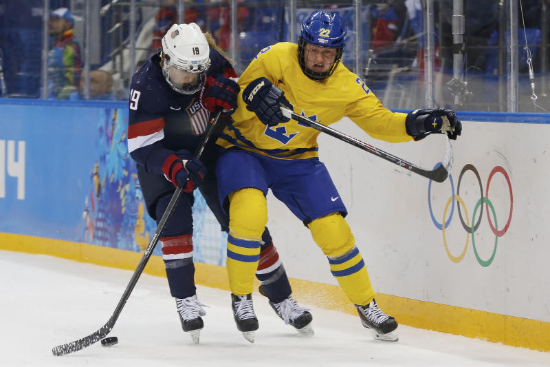 Gigi Marvin of the United States and Emma Eliasson of Sweden battle fro control of the puck during the second period of the 2014 Winter Olympics women's semifinal ice hockey game at Shayba Arena Monday, Feb. 17, 2014, in Sochi, Russia. (AP Photo/Petr David Josek)