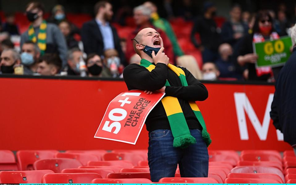 Manchester United fan reacts from their seat whilst holding a protest placard - Getty