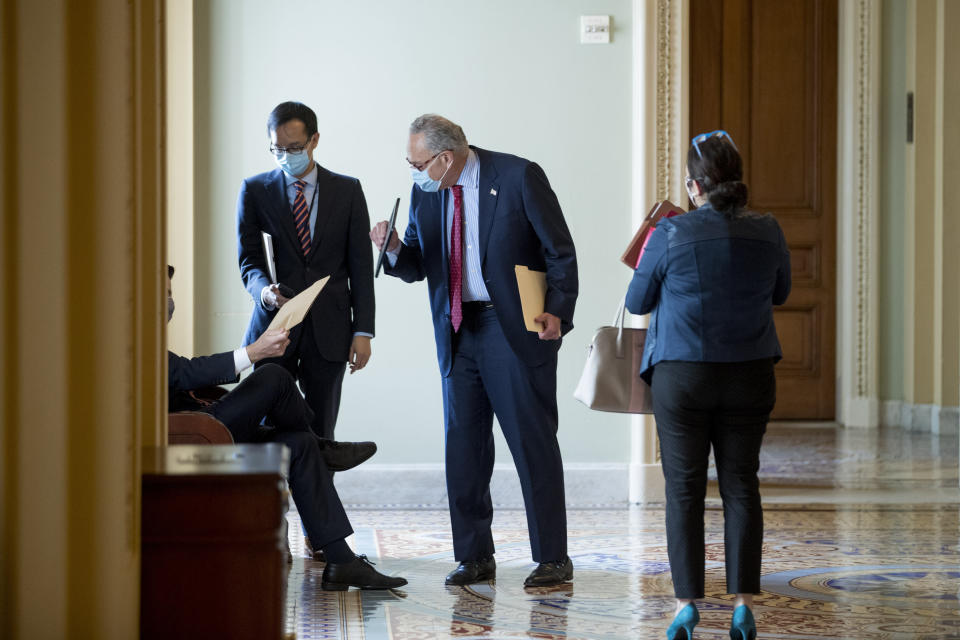 Senate Minority Leader Sen. Chuck Schumer of N.Y. speaks with aides before a meeting with House Speaker Nancy Pelosi of Calif., Treasury Secretary Steven Mnuchin, and White House Chief of Staff Mark Meadows as they continue to negotiate a coronavirus relief package on Capitol Hill in Washington, Tuesday, Aug. 4, 2020. (AP Photo/Andrew Harnik)