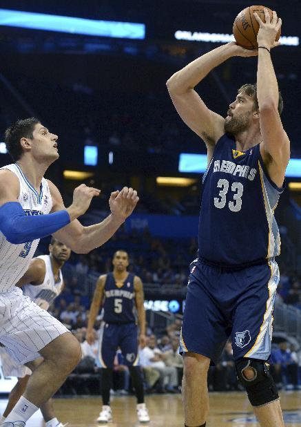 Memphis Grizzlies center Marc Gasol (33) goes up for a shot in front of Orlando Magic center Nikola Vucevic during the first half of an NBA basketball game in Orlando, Fla., Wednesday, Feb. 12, 2014. (AP Photo/Phelan M. Ebenhack)