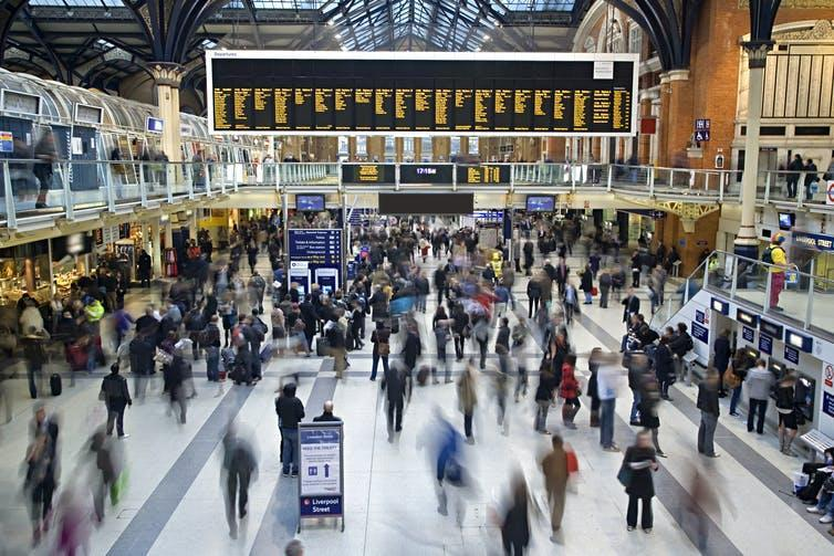 Liverpool Street Station in London as crowds of people rush through.