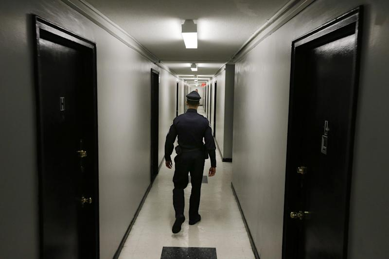 In this Tuesday, April 15, 2014 photograph, Camden County Metro police Sgt. Raphael Thornton walks in a hallway of the high-rise apartment building, Northgate I in Camden, N.J. Crime has dropped in Camden since the new police department rolled into town a year ago, but it remains far more dangerous than most cities. (AP Photo/Mel Evans)