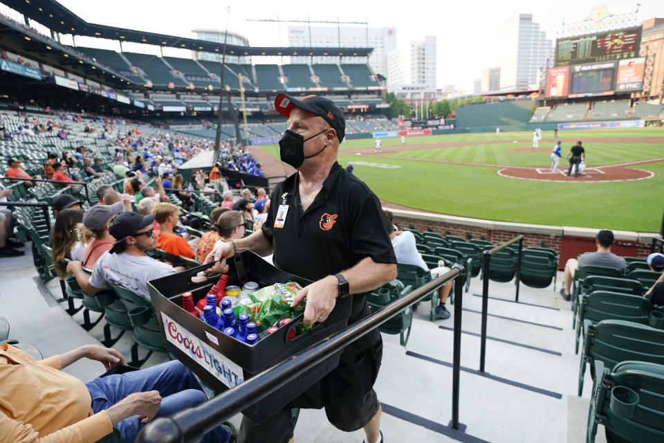 A vendor makes his way up an isle behind home plate at Oriole Park at Camden Yards during the first inning of a baseball game between the Baltimore Orioles and the Toronto Blue Jays, Tuesday, July 6, 2021, in Baltimore. It would be premature to say that the scene at major league ballparks has completely returned to normal, but there's no question this season has been a step in that direction — perhaps most crucially for the people who work there. (AP Photo/Julio Cortez)
