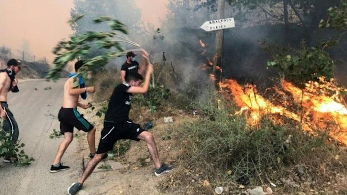 People attempt to put out a fire in the mountainous Tizi Ouzou province, east of Algiers, Algeria August 10, 2021