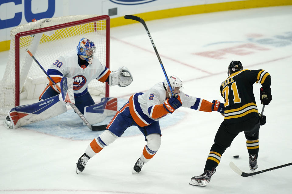 New York Islanders defenseman Nick Leddy, center, cannot stop Boston Bruins left wing Taylor Hall, right, from shooting his winning goal against Islanders goaltender Ilya Sorokin, left, in the overtime period of an NHL hockey game, Monday, May 10, 2021, in Boston. (AP Photo/Elise Amendola)