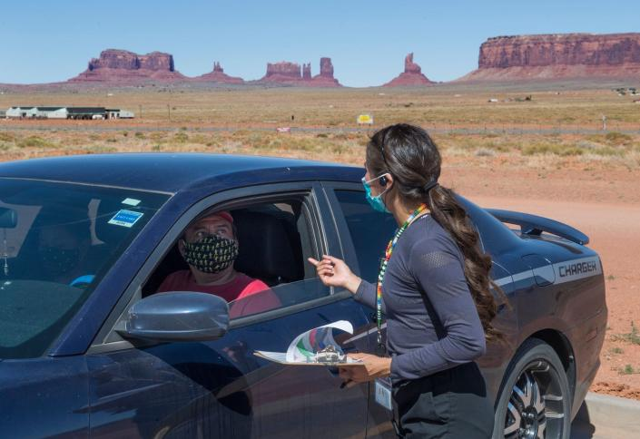 "<span class=""caption"">Medics consult with a drive-in patient at a COVID-19 testing center in the Navajo Nation town of Monument Valley, Arizona. Navajo Nation President Jonathan Nez said weeks of delays in delivering coronavirus aid to Native American tribes exacerbated the outbreak.</span> <span class=""attribution""><a class=""link rapid-noclick-resp"" href=""https://www.gettyimages.com/detail/news-photo/medical-staff-consult-with-a-navajo-indian-man-at-a-covid-news-photo/1214464307?adppopup=true"" rel=""nofollow noopener"" target=""_blank"" data-ylk=""slk:Getty Images / Mark Ralston"">Getty Images / Mark Ralston</a></span>"