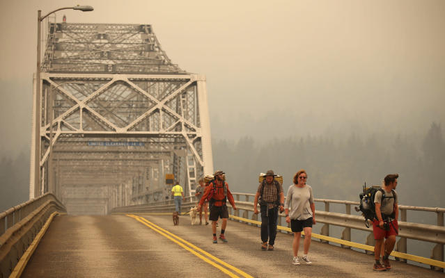 <p>Pedestrians walk off the Bridge of the Gods, which spans the Columbia River between Washington and Oregon states, as smoke from the Eagle Creek wildfire obscures the Oregon hills in the background near Stevenson, Wash., on Sept. 6, 2017. (Photo: Randy L. Rasmussen/AP) </p>