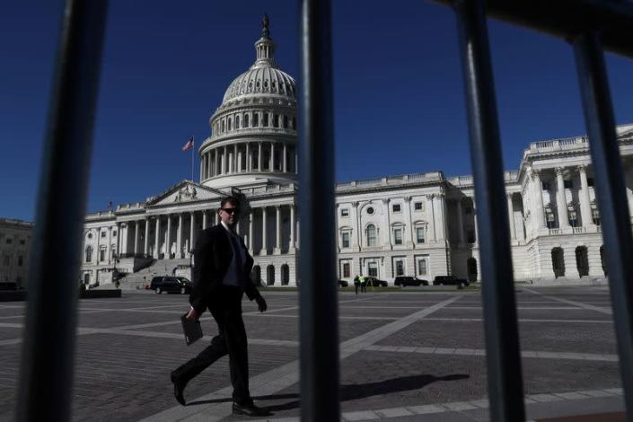 FILE PHOTO: A man walks past the U.S. Capitol building as a government shutdown looms in Washington