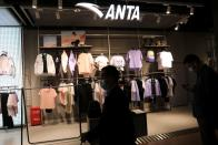People walk past a store of Chinese sportswear brand Anta in Beijing