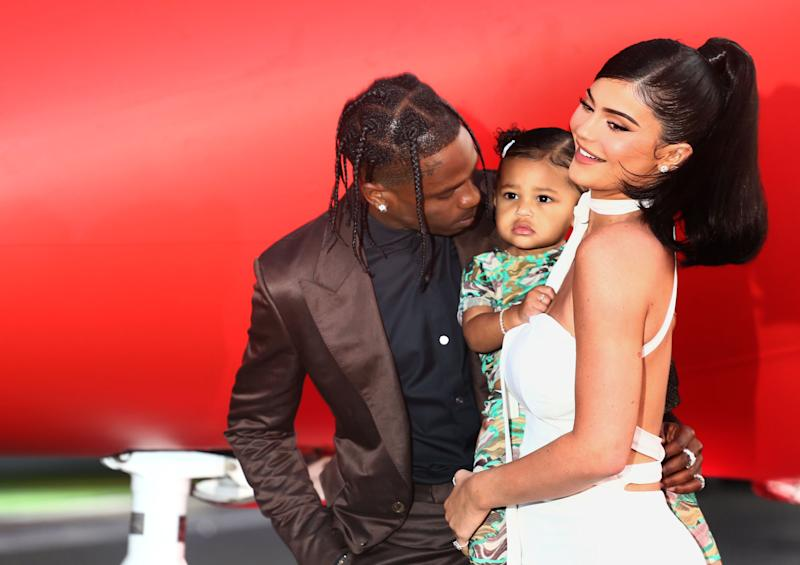 Travis Scott puts his arm around Kylie Jenner who is holding Stormi