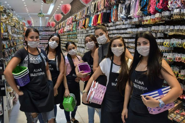 Shop sellers wear masks in the Brazilian city of Sao Paulo, where a state of emergency has been declared over the coronavirus pandemic