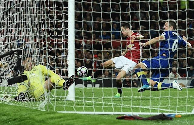 Everton's defender Phil Jagielka (R) jumps to block a shot from Manchester United's midfielder Ander Herrera (C as Everton's goalkeeper Joel Robles lays in his goal injured during the English Premier League football match on April 4, 2017 (AFP Photo/Oli SCARFF )