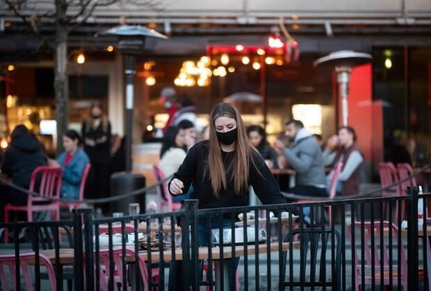A server clears a table on a patio at a restaurant in Vancouver.