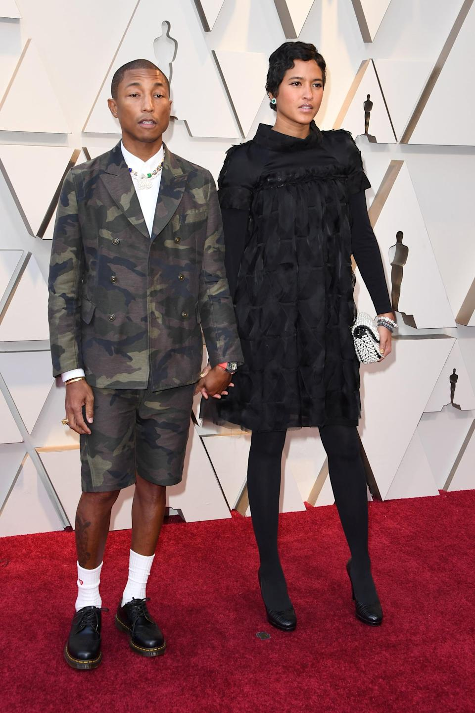 <p>Pharrell is wearing a camo shorts suit, and Helen is wearing a black dress and tights.</p>