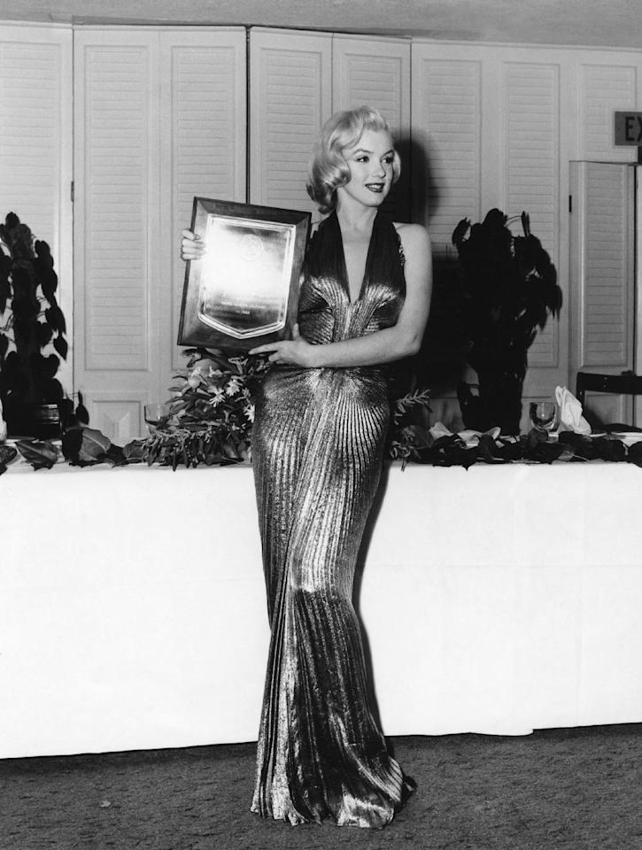 "In this March 1953 publicity photo provided by Running Press, Marilyn Monroe receives an award from Photoplay magazine at the Beverly Hills Hotel, in Beverly Hills, Calif. She is named ""Fastest Rising Star of 1952,"" and her choice of attire overshadows the event. The entire gown was made from ""one complete circle of fabric."" (AP Photo/Courtesy Running Press)"
