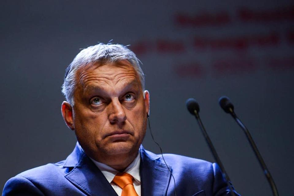 Viktor Orbán in a navy suit and orange tie looks up while at a press conference