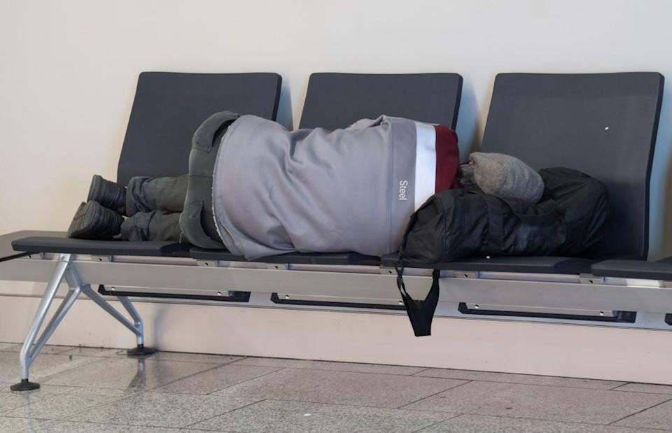 A man sleeps on chairs in an airport.
