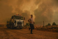 A man runs, in the fire-devastating Sirtkoy village, near Manavgat, Antalya, Turkey, Sunday, Aug. 1, 2021. More than 100 wildfires have been brought under control in Turkey, according to officials. The forestry minister tweeted that five fires are continuing in the tourist destinations of Antalya and Mugla. (AP Photo)
