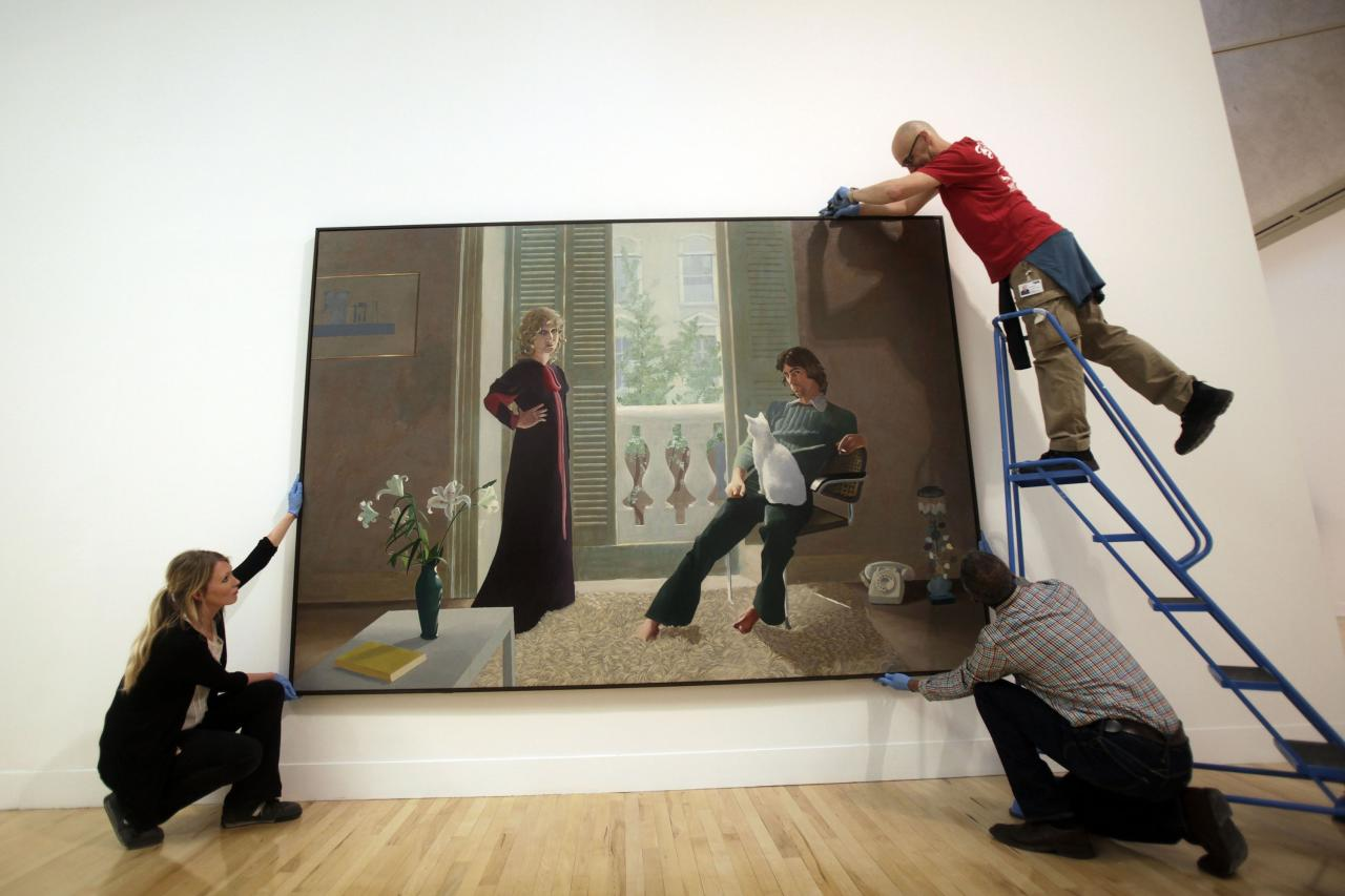 LONDON, UNITED KINGDOM - MAY 13: Workers adjust David Hockney's Mr and Mrs Clark and Percy for display at the Walk through British Art exhibition at Tate Britain on May 13, 2013 in London, England. Visitors will experience a completely new presentation of the world's greatest collection of British art, the national collection of British art will be displayed in a continuous and purely chronological display from the 1500s to the present day. (Photo by Warrick Page/Getty Images)