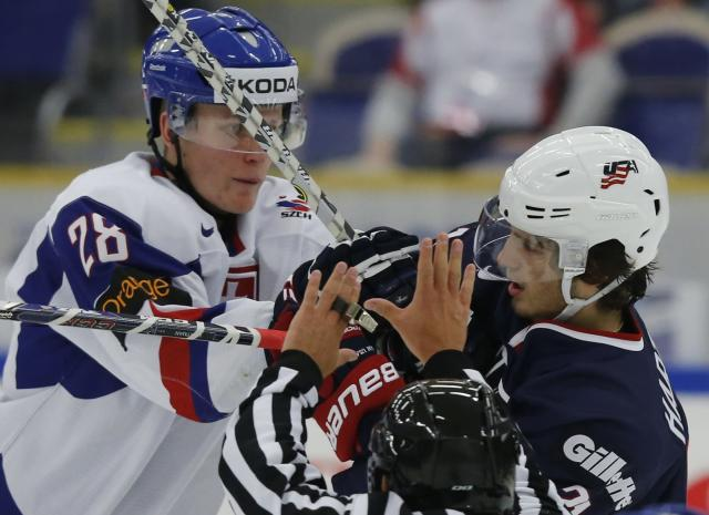 A linesman tries to break up the fight between Slovakia's Pavol Skalicky (L) and Ryan Hartman of the U.S during the second period of their IIHF World Junior Championship ice hockey game in Malmo, Sweden, December 28, 2013. REUTERS/Alexander Demianchuk (SWEDEN - Tags: SPORT ICE HOCKEY)