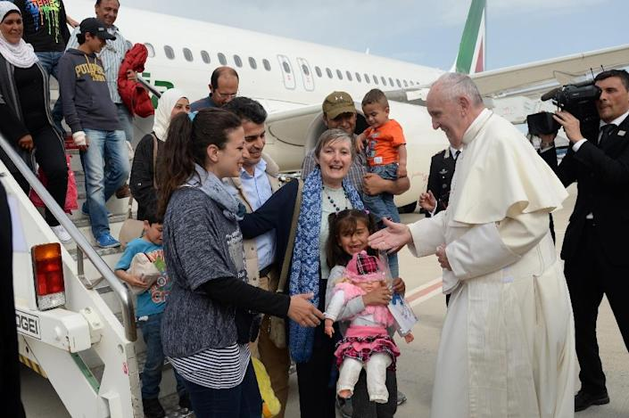 Pope Francis welcomes a group of Syrian migrants at Rome's Ciampino airport on April 16, 2016 following a visit to the Greek island of Lesbos (AFP Photo/Filippo Monteforte)
