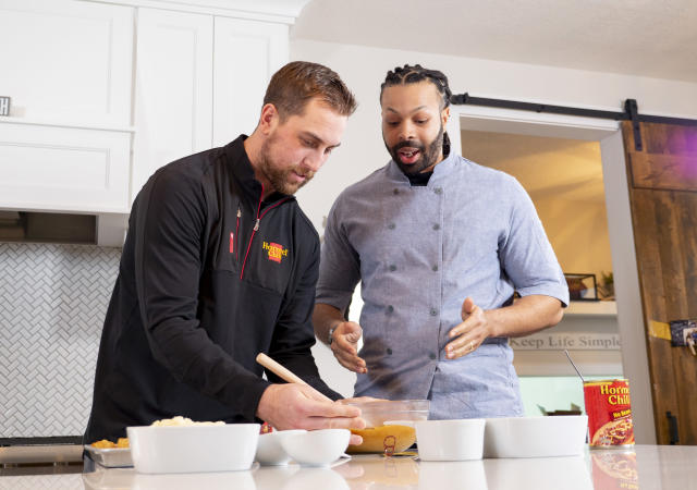 In a photo provided by Hormel Foods, Minnesota Vikings wide receiver Adam Thielen, left, and chef Kenneth Temple prepare a Minnesota-inspired chili dip Jan. 15, 2019, in Austin, Minn. The beautiful thing about it is chili and football go hand in hand, Temple says, noting Hormel was a partner with the NFL as far back at the 1950s. At tailgates or with friends at a viewing party or wherever, it is easy to accommodate a larger crowd. (Hormel Foods via AP)