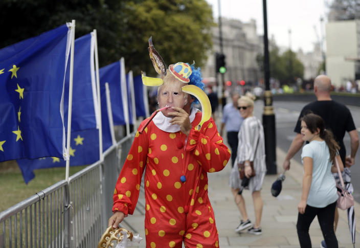 An Anti-Brexit supporter wearing a Boris Johnson mask is seen near the Houses of Parliament in London, Wednesday, Aug. 28, 2019. British Prime Minister Boris Johnson asked Queen Elizabeth II on Wednesday to suspend Parliament, throwing down the gauntlet to his critics and causing outrage among opposition leaders who will have even less time to thwart a no-deal Brexit. (AP Photo/Matt Dunham)