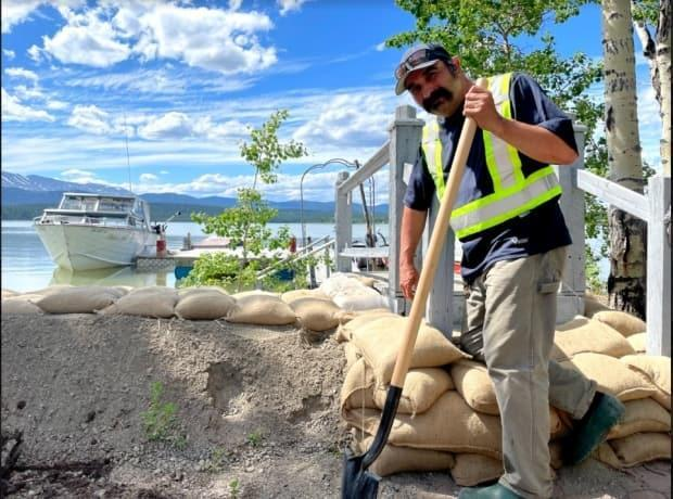 Gil Bradet stacks sandbags on the shores of Marsh Lake at South M'Clintock on Tuesday. 'We are facing an extraordinary amount of water,' Bradet said. 'It's not abnormal because we are on a lake. But I've never seen the water come up so fast and this high at this time of year.' (Vincent Bonnay/Radio-Canada - image credit)