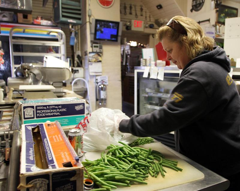 In this photo taken Thursday Dec. 6, 2012, owner of Robie's Country Store and Deli Debbie Chouinard works on cutting up green beans.  (AP Photo/Jim Cole)