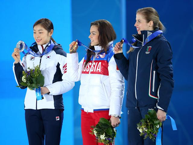 SOCHI, RUSSIA - FEBRUARY 21: (L-R) Silver medalist Yuna Kim of South Korea, Gold medalist Adelina Sotnikova of Russia and Bronze medalist Carolina Kostner of Italy celebrate during the medal ceremony for the Women's Free Figure Skating on day fourteen of the Sochi 2014 Winter Olympics at Medals Plaza on February 21, 2014 in Sochi, Russia. (Photo by Quinn Rooney/Getty Images)