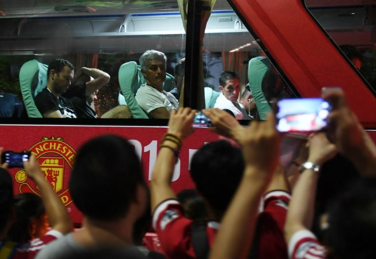 Manchester United coach Jose Mourinho (top C) looks at fans from the team bus after a training session in Beijing on July 24, 2016, a day before the 2016 International Champions Cup match between his side and Manchester City