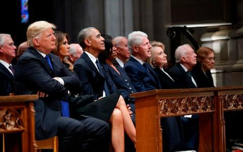 Donald Trump, Barack Obama, Bill Clinton and Jimmy Carter and their wives sit together for George H W Bush's funeral - Credit: ALEX BRANDON/AFP