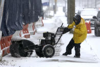 A man works to turn his snow-clearing machine Sunday Jan. 31, 2021 in Philadelphia. After days of frigid temperatures, the Northeast is bracing for a whopper of a storm that could dump well over a foot of snow in many areas and create blizzard-like conditions. (AP Photo/Jacqueline Larma)