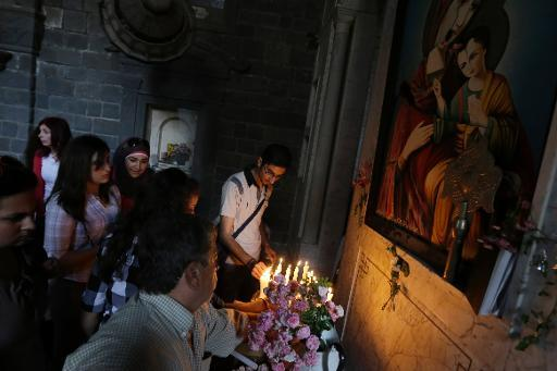 People light candles under a damaged painting of the Virgin Mary at the Syriac Orthodox Um al-Zinar church in the Old City of Homs, on May 12, 2014