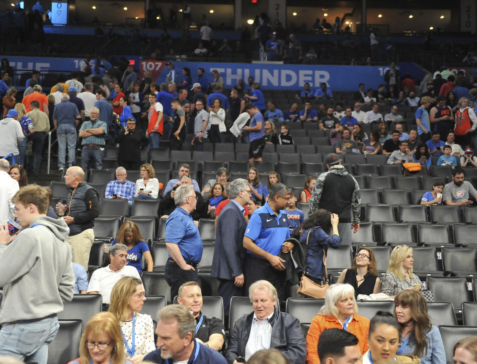 Basketball fans clear out after it is announced that an NBA basketball game between Oklahoma City Thunder and Utah Jazz in Oklahoma City has been postponed, Wednesday, March 11, 2020. (AP Photo/Kyle Phillips)